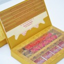 Gold box containing red satin scroll and chocolates